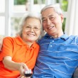 Senior Chinese Couple Watching TV On Sofa At Home — Stock Photo