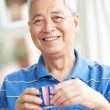 Senior Chinese Man Drinking Tea On Sofa At Home — Stockfoto
