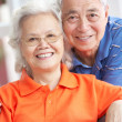 Stock Photo: Senior Chinese Couple Relaxing On Sofa At Home