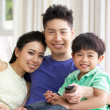 Chinese Family Sitting And Watching TV On Sofa Together — Stockfoto