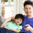 Royalty-Free Stock Photo: Chinese Father And Son Sitting And Watching TV On Sofa Together