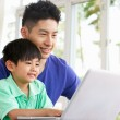 Chinese Father And Son Sitting At Desk Using Laptop At Home - 图库照片