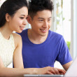 Young Chinese Couple Sitting At Desk And Using Laptop At Home — Stock Photo