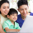 Chinese Family Sitting At Desk Using Laptop At Home — Stock fotografie