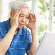 Worried Senior Chinese Man Sitting At Desk Using Laptop At Home — Foto de Stock