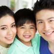 Stock Photo: Head And Shoulders Portrait Of Chinese Family Together At Home
