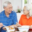 Senior Chinese Couple Sitting At Home Eating Meal — Stock Photo #24444183
