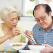 Senior Chinese Couple Sitting At Home Eating Meal — Stock Photo