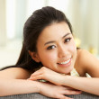 Young Chinese Woman Relaxing On Sofa At Home — Stock Photo #24444407