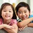Two  Chinese Children Relaxing On Sofa At Home - Stock Photo