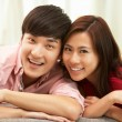 Young Chinese Couple Relaxing On Sofa At Home — Stock Photo #24444435