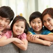 Stock Photo: Chinese Family Sitting And Relaxing On Sofa Together At Home