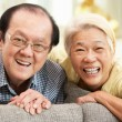 Senior Chinese Couple Relaxing On Sofa At Home - Stock Photo