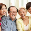 Stock Photo: Portrait Of Chinese Parents With Adult Children Relaxing At Home