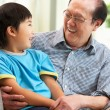 Stock Photo: Chinese Grandfather And Grandson Relaxing On Sofa At Home