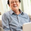 Senior Chinese Man Using Laptop Whilst Relaxing On Sofa At Home — Stock Photo