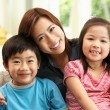 Chinese Mother And Children Sitting On Sofa At Home Together — Stock Photo