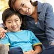 Chinese Mother And Son Sitting On Sofa At Home Together - Foto Stock