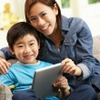 Chinese Mother And Son Using Tablet Computer Whilst Sitting On S - Foto Stock