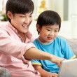 Chinese Father And Son Using Laptop Whilst Relaxing On Sofa At H — Stock Photo