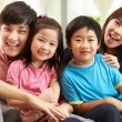 Stock Photo: Chinese Family Relaxing On Sofa At Home