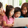 Chinese Family Using Laptop Whilst Relaxing On Sofa At Home - Stockfoto