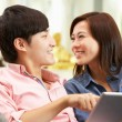 Young Chinese Couple Using Digital Tablet Whilst Relaxing On Sof — Stock Photo