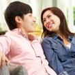 Stock Photo: Young Chinese Couple Relaxing On Sofa At Home