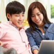 Young Chinese Couple Using Laptop Whilst Relaxing On Sofa At Hom — Stock Photo