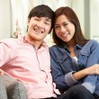 Young Chinese Couple Relaxing On Sofa At Home — Stock Photo