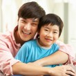 Chinese Father And Son Relaxing On Sofa At Home - Stock Photo