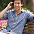 Young Chinese Man Relaxing On Park Bench Talking On Mobile Phone — Stock Photo