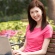 Young Chinese Woman Using Laptop Whilst  Relaxing On Park Bench — Stock Photo