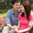 Young Chinese Couple Relaxing On Park Bench Together — ストック写真