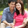 Young Chinese Couple Relaxing On Park Bench Together — Stockfoto