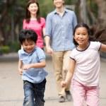 Chinese Family Walking Through Park With Running Children — Stock Photo