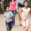 Chinese Family Walking Through Park With Running Children — Stock Photo