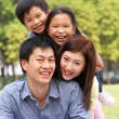 Young Chinese Family Relaxing In Park Together — Stock Photo #24445987