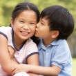 Stock Photo: Portrait Of Chinese Boy And Girl Sitting In Park Together