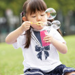 Young Chinese Girl In Park Blowing Bubbles — Stock Photo