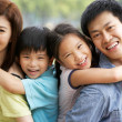 Portrait Of Chinese Family Relaxing In Park Together - Stock Photo