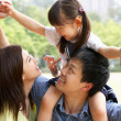 Chinese Family Giving Daughter Ride On Shoulders In Park — Stock Photo #24446331