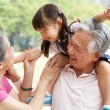 Stock Photo: Chinese Grandparents Giving Granddaughter Ride On Shoulders
