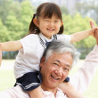 Royalty-Free Stock Photo: Chinese Grandfather Giving Granddaughter Ride On Shoulders In Pa