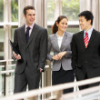 Stock Photo: Three Business Colleagues Having Discussion Whilst Walking Outsi