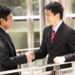 图库照片: Two Chinese Businessmen Shaking Hands Outside Office