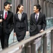 Three Business Colleagues Having Discussion Whilst Walking Outsi - Stock Photo