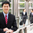 Portrait Of Chinese Businessman Outside Office With Colleagues I - Stock Photo