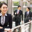 Portrait Of Chinese Businesswoman Outside Office With Colleagues - Stock Photo