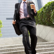 Chinese Businessman Rushing Down Steps Carrying Bag And Takeaway - Stock Photo